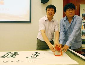 胡锡进和陈彤总编辑在题字上盖章