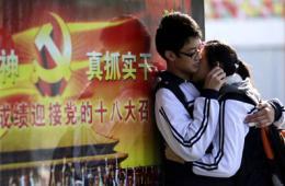 """学生情侣在""""十八大""""宣传海报前拥抱"""