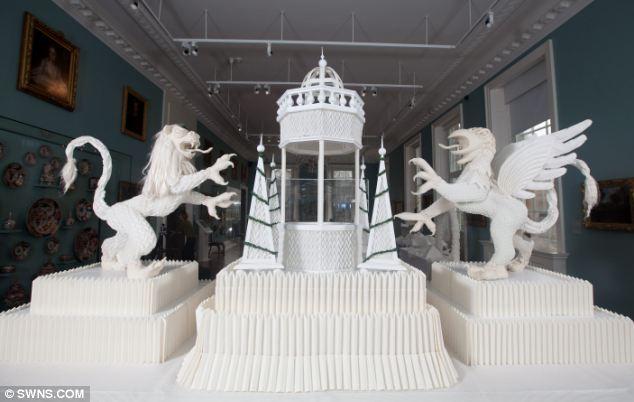 """【环球网综合报道】据英国《每日邮报》1月31日消息,近日,西班牙加泰罗尼亚艺术家琼•萨拉(Joan Sallas)在英国巴思市赫尔本博物馆展出用亚麻餐纸折叠而成的艺术品。整个作品长达23英尺(约合7米),其巧夺天工的""""神兽""""和""""山脉""""将餐巾纸折叠法推上了一个新高度。   据报道,中心作品是一座精致的高塔以及喷泉,两边分别为希腊神话中的怪兽""""格里芬"""",以及一头狮子。展出的作品中还包括3米长的蛇、孔雀、山峦、乌龟等。   琼"""