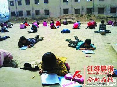 小学生趴在地上参加月考。(图片来自网络)