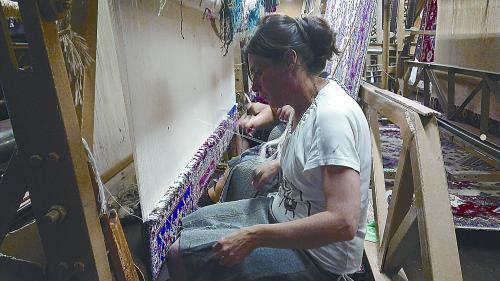 正在编织地毯的女工和申奥会徽。