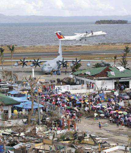 """13日,在菲律宾遭受台风""""海燕""""袭击灾情最严重的莱特省塔克洛班市,灾民在机场外等待离开。"""