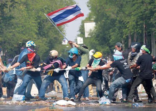 2日,在泰国首都曼谷的政府大厦附近,抗议者用绳子拉开警方设置的路障。