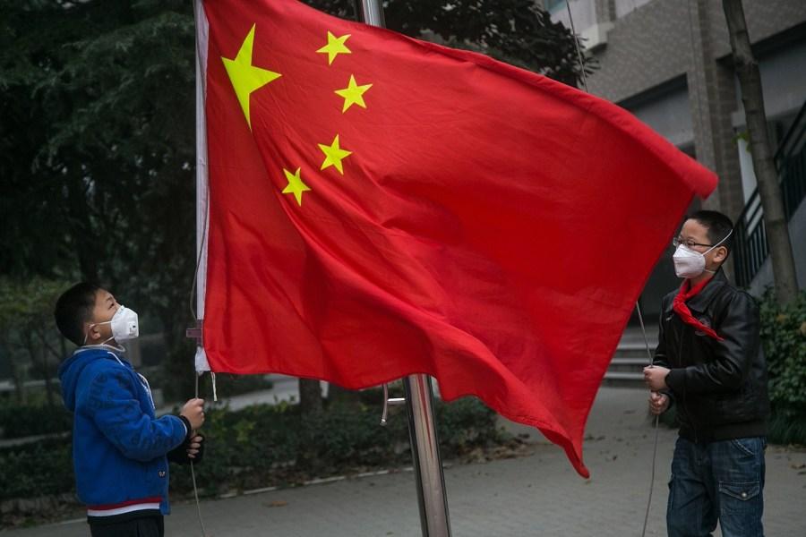 升国旗仪式被迫移至教室内举行,两名戴着口罩的旗手在操场上升旗.