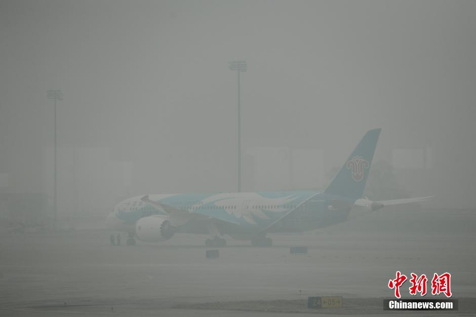 2月26日,北京首都国际机场,候机乘客透过玻璃观看笼罩在雾霾中的飞机.