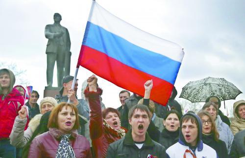 克里米亚6日宣布将就是否加入俄罗斯进行全民公投。图为当地民众举着俄罗斯国旗参加集会。