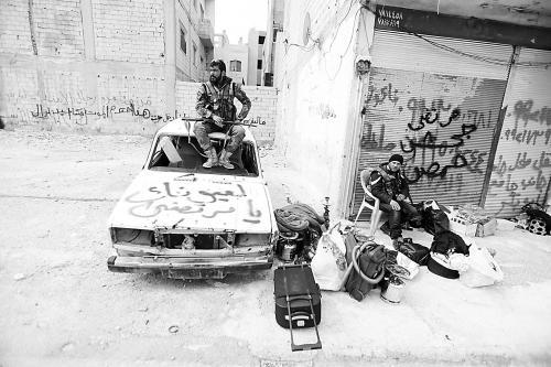 16日,攻下耶布鲁德后,两名叙利亚共和国卫队士兵在城中休整。 (焦翔摄)