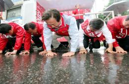 韩国首尔市长候选人冒雨跪地拉票