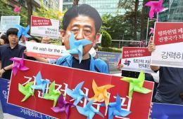 韩国民众扮安倍嘴衔风车 反对日解禁集体自卫权