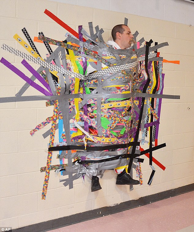 美国小学校长履行承诺 让学生把自己粘墙上