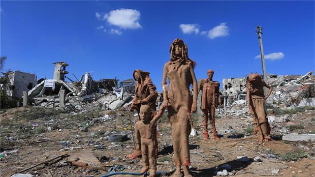 艺术家在巴以冲突废墟上建难民雕像群