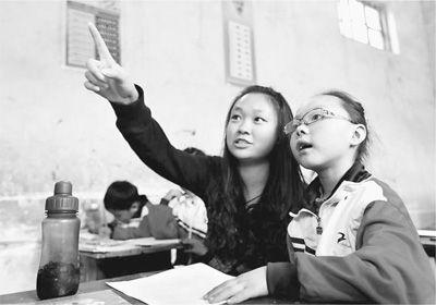 爱心支教老师正在辅导一名女生学习绘画基本知识。 人民视觉