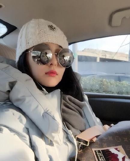 照片中,范冰冰红唇大墨镜,头戴可爱小白帽,坐在车内穿着厚厚的羽绒服