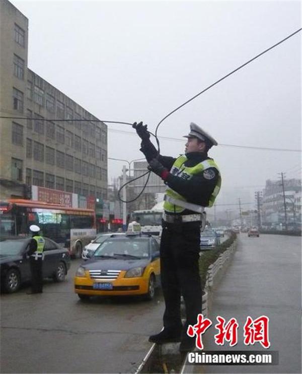 交警雨中托举电缆2个多小时让车通行