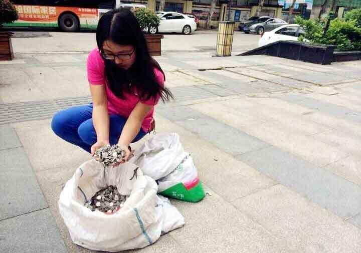 武汉/2015年5月2日,武汉市民吴女士骑着电动车拖着2个蛇皮袋前往...
