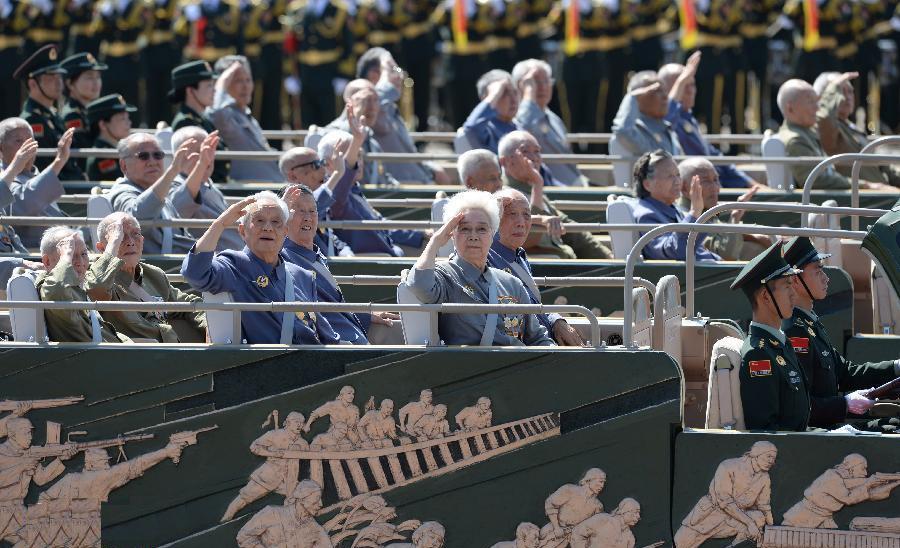 抗战老兵乘车方队通过天安门时,老兵们纷纷向主席台敬礼致意。