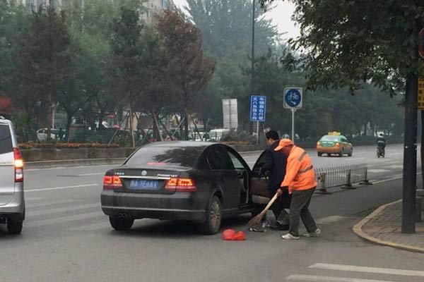 轿车男子街头撒垃圾 老年环卫工默默打扫