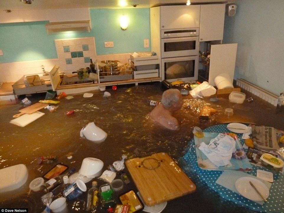英国暴雨导致房屋被淹 72岁老人无惧在厨房里游泳