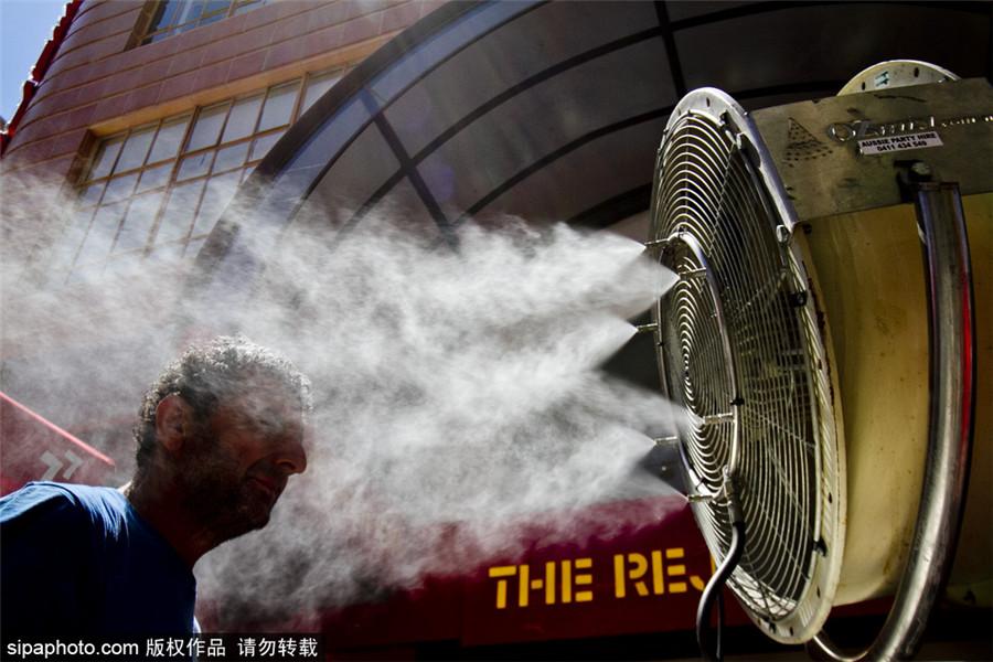 """""""水深火热""""南半球 澳大利亚高温难耐街头摆降温神器"""
