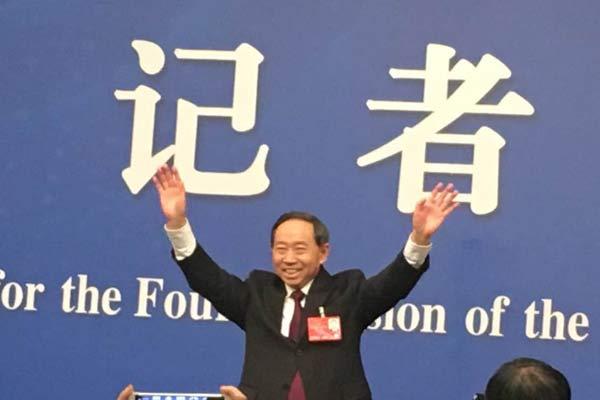 教育部部长袁贵仁为了方便记者拍照起身招手