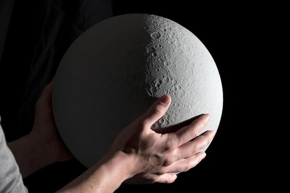 """【环球科技综合报道】拿""""月球""""当台灯?这听起来实在是太荒诞了,怎么可能呢?月球那么大!但是大家别急着反驳,有位手工大师就把这个看起来荒诞的事情变成了事实,怎么回事呢?   """"MOON"""" 产品设计师 Oscar Lhermitte 和 Kudu 设计工作室出品的这盏月球灯,以1:2000万比例尺严格按照NASA公布的数据制作。环绕它旋转的光源可以手动设定,也可以完全与真实的月球同步。(kudustudio."""