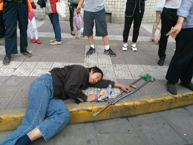 男子晕倒西安街头 接过钱后瞬间不晕