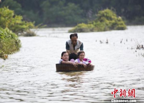 江西暴雨过后 村民用木桶推孙女上学