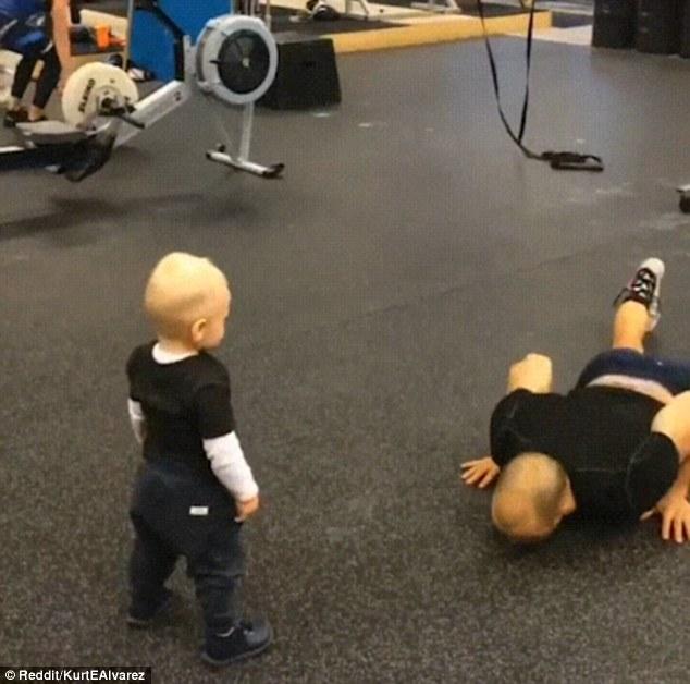 学步男童模仿爸爸健身动作萌态尽显
