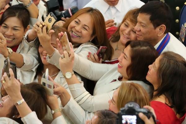 菲律宾总统杜特尔特任后首访国家警察署 与女客自拍合影