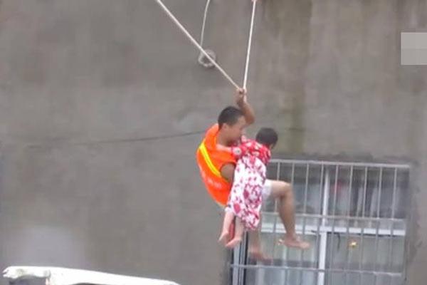 消防员洪流里奋力救小孩