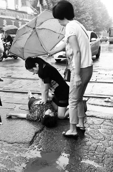 """郑州女护士雨中跪地为伤者施救 被称""""最美女护士"""""""