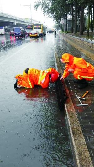 北京抢险人员匍匐积水中排水 脸离脏水几毫米