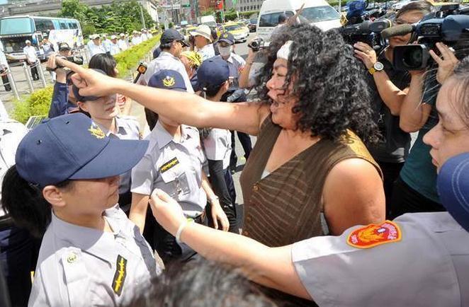 """莱芜论坛:活动前,在凯道上抗议的少数民族转型正义同盟成员们挺进到南广场旁的凯道上举布条抗议,高喊""""族群代表加入我们,不要被摸头""""。"""