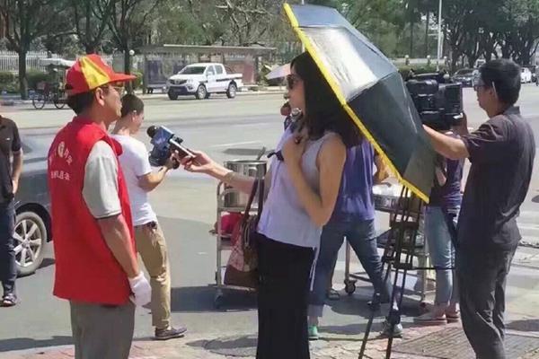 厦门一女记者戴墨镜打伞采访救灾志愿者被停职(图)