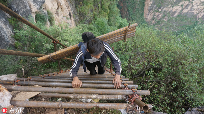村民背1500根钢管上山 悬崖走壁造天梯