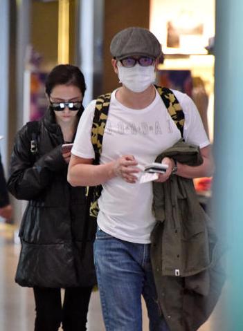 张靓颖冯轲现身机场 一路玩手机变低头族
