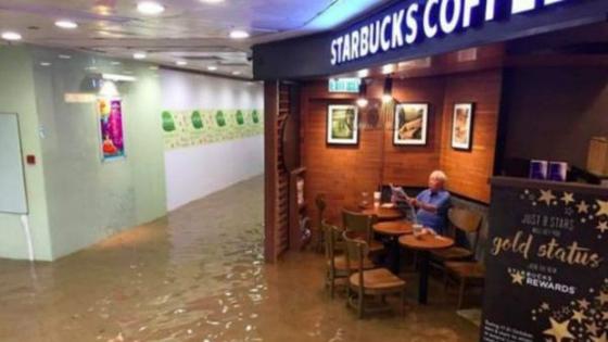 外媒:老伯洪水中淡定喝咖啡成网红 被