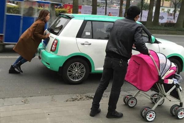美女推轿车走数百米 老公一旁淡定带娃