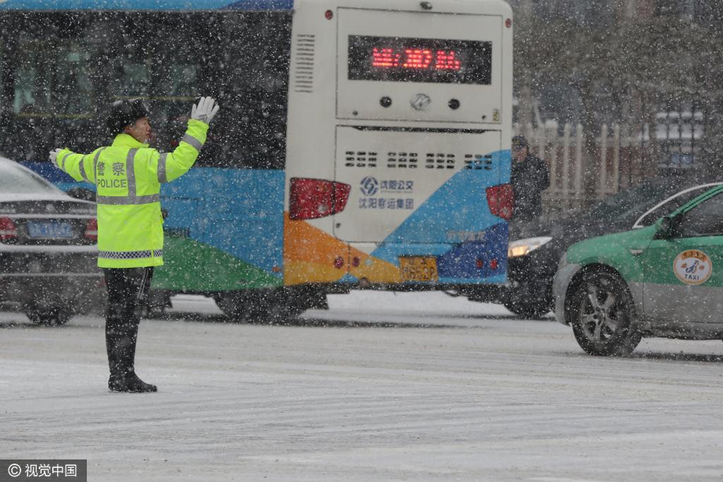 沈阳:女交警大雪天气中指挥交通成靓丽风景线