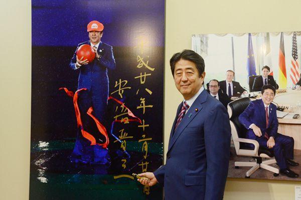 """安倍晋三参观新闻图片展 为""""超级马里奥""""留影签名"""