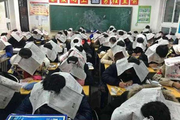 中学教师为防作弊让学生头戴报纸考试