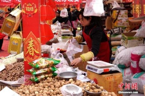 """资料图:2015年2月5日,春节临近,西安的年货市场也开始""""红火""""起来,前来采购新年喜庆饰品、酒水饮料和食品的市民络绎不绝。张远 摄"""
