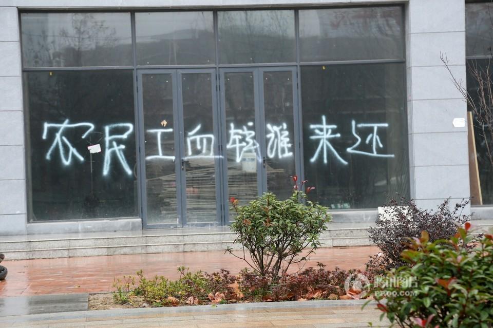 郑州街头百米商铺变身讨薪墙