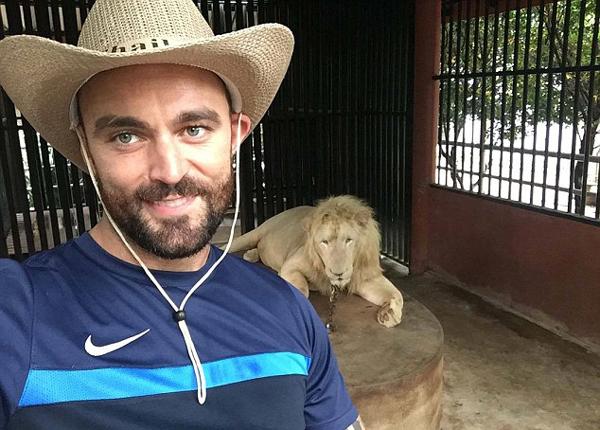 美国一男子动物园里摸狮子被其吓得落荒而逃