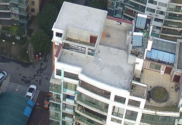 湖北一小区11层高楼上现违建 城管用无人机取证