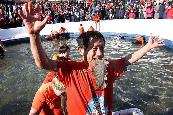 韩年度冰钓大赛如期举行 垂钓者嘴中叼鱼庆祝