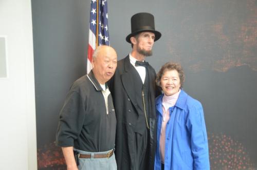 """来自卡森市的第二代余姓华裔夫妇Bill & Margie Yee,在尼克松图书馆与""""林肯总统""""合照。(美国《世界日报》/王善言 摄)"""