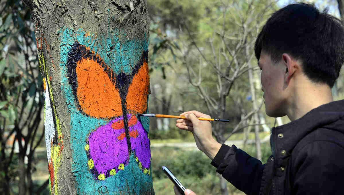 大学生公园树干作画 为春天增添生机