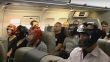 多位乘客戴头盔乘坐美联邦航班