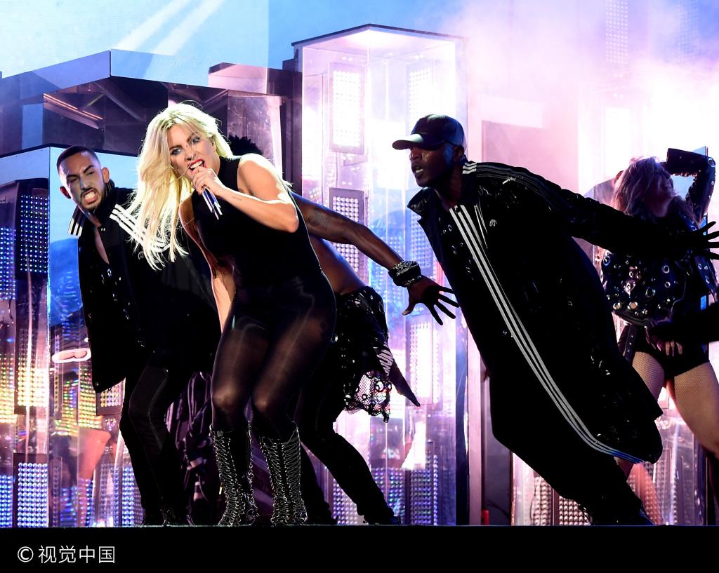 Lady Gaga变黑衣女郎狂野热舞 获肌肉男托举